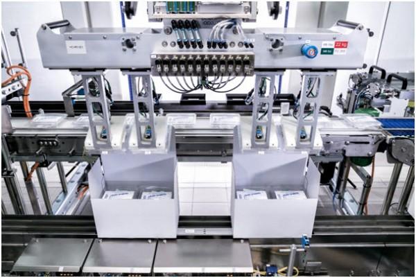 유입되는 라벨이 붙은 클램쉘은 사전 분류되어 F4 로봇에 의해 적재대로 이송된다. 일단 상자가 만들어지고 클램쉘이 내부에 놓여지면 가변 데이터(다양한 데이터)가 인쇄 된 라벨이 붙고 상자가 밀봉된다.