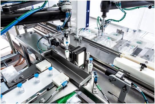 F4 로봇이 분리 된 바이알을 클램쉘 트레이에 적재한다. 바이알을 적재하기 전에 F4 로봇은 투명 라벨의 변수 데이터를 읽고 확인하는 카메라 앞에 있는 터닝 스테이션에 바이알을 놓는다.